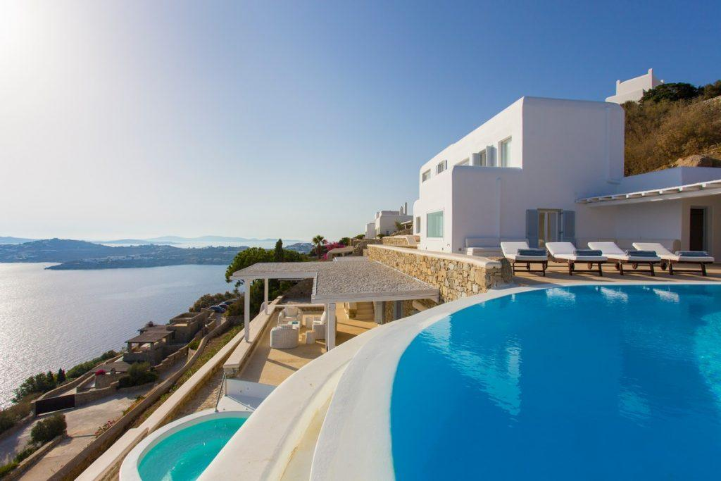 white and stone villa with large pool
