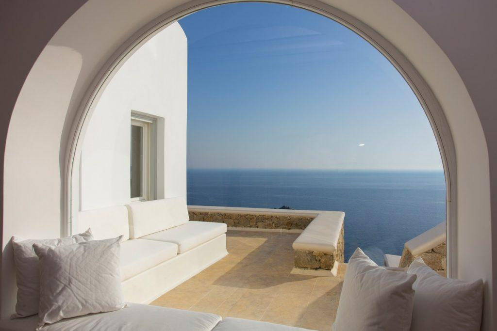 circular window with a comfortable sofa and a view of the glistening sea