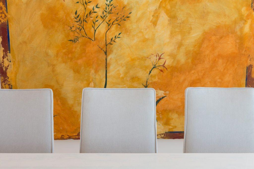 table and white chairs that fit perfectly along the bright yellow wall with drawing details