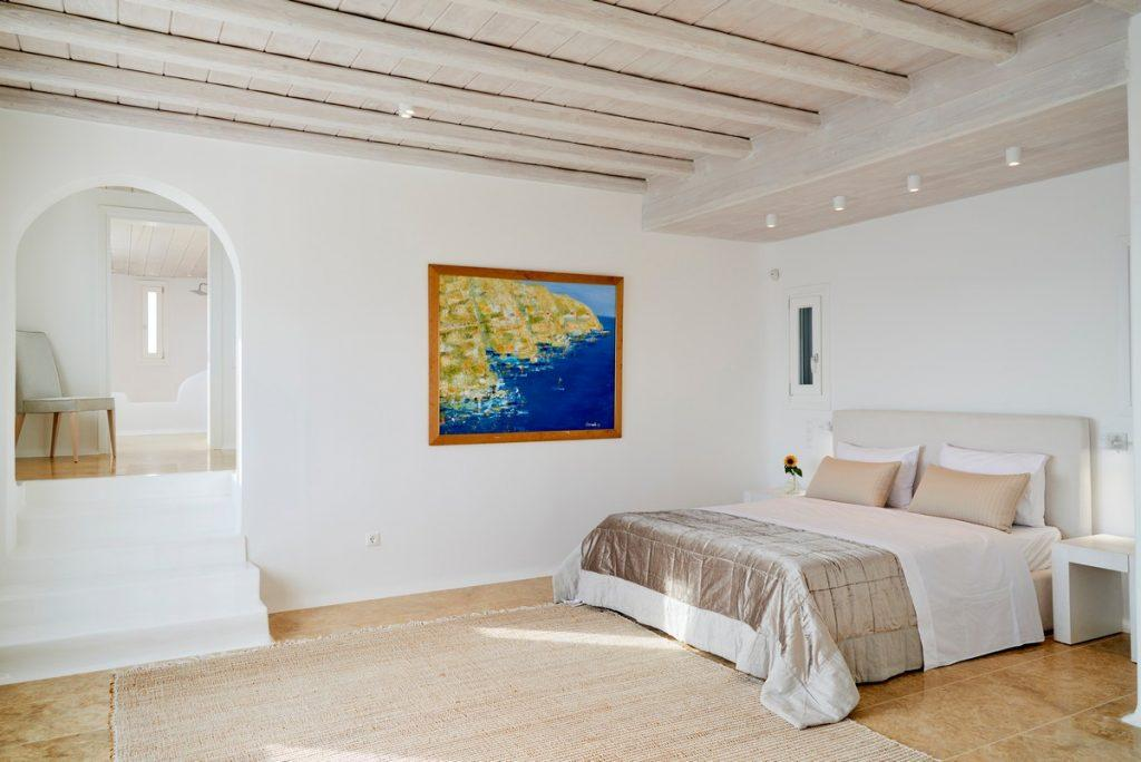 white walls of the room with a comfortable bed and a bedside table in the corner