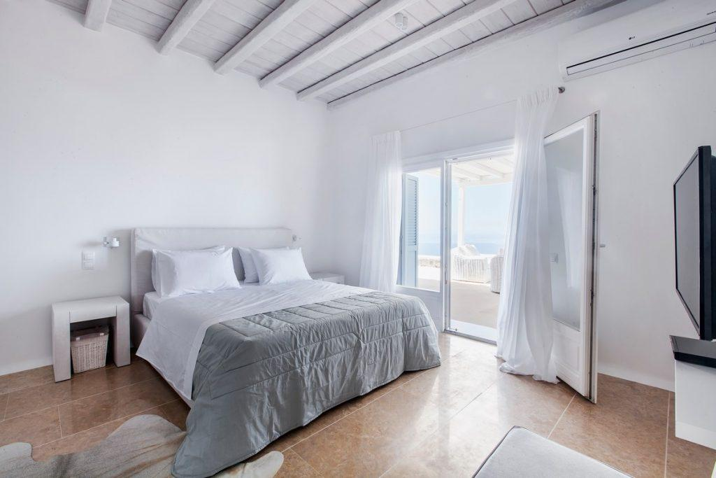 white walls of the room with a comfortable bed and a special detail of the gray cover