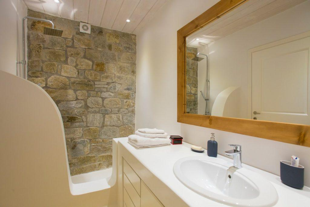 bathroom with decorative stone wall and shower