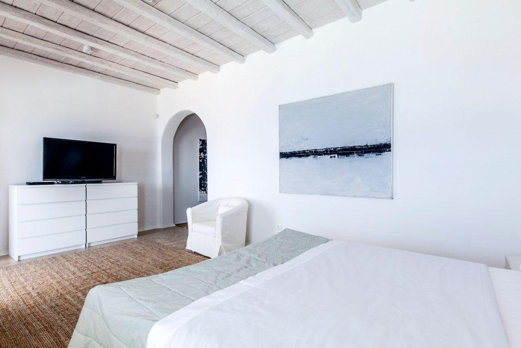 bedroom with white wooden shelf and large TV