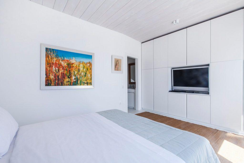 bedroom with huge white closet and TV