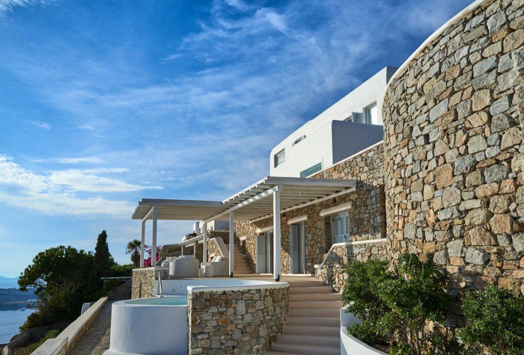 clear skies above a luxurious villa of stone walls and a white canopy
