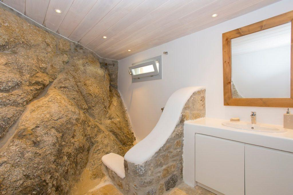 stone bathroom walls with shower and white sink