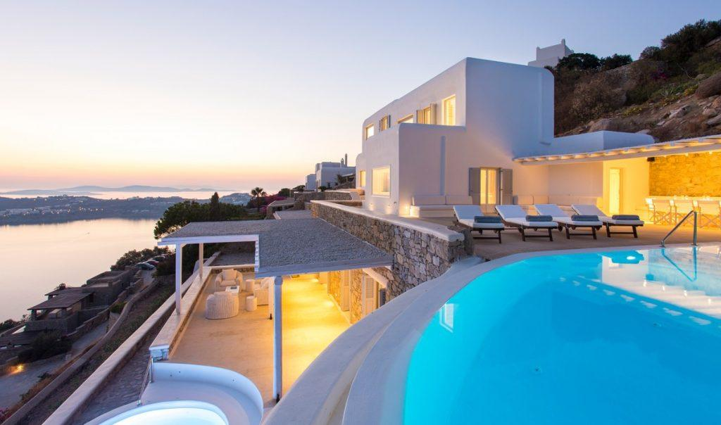 white villa dimly lit on two levels overlooking the sea and pool