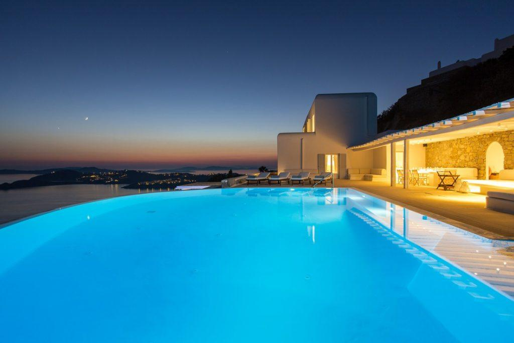 view of the dimly lit villa with beautiful sunset over the sea