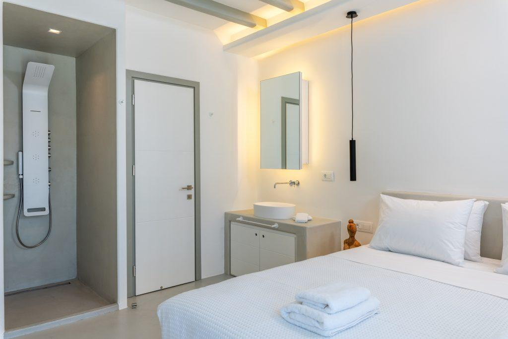 bedroom with white walls and white sink with lighted mirror