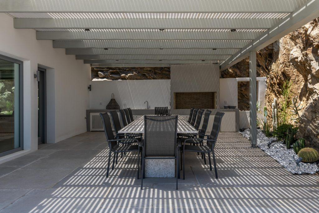 lighted stone walls decorated with cactus plants and a table with black chairs ideal for hanging out with friends