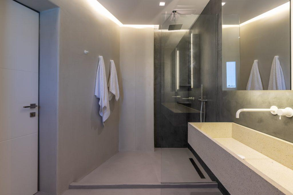 glass shower and ceramic sink with large mirror
