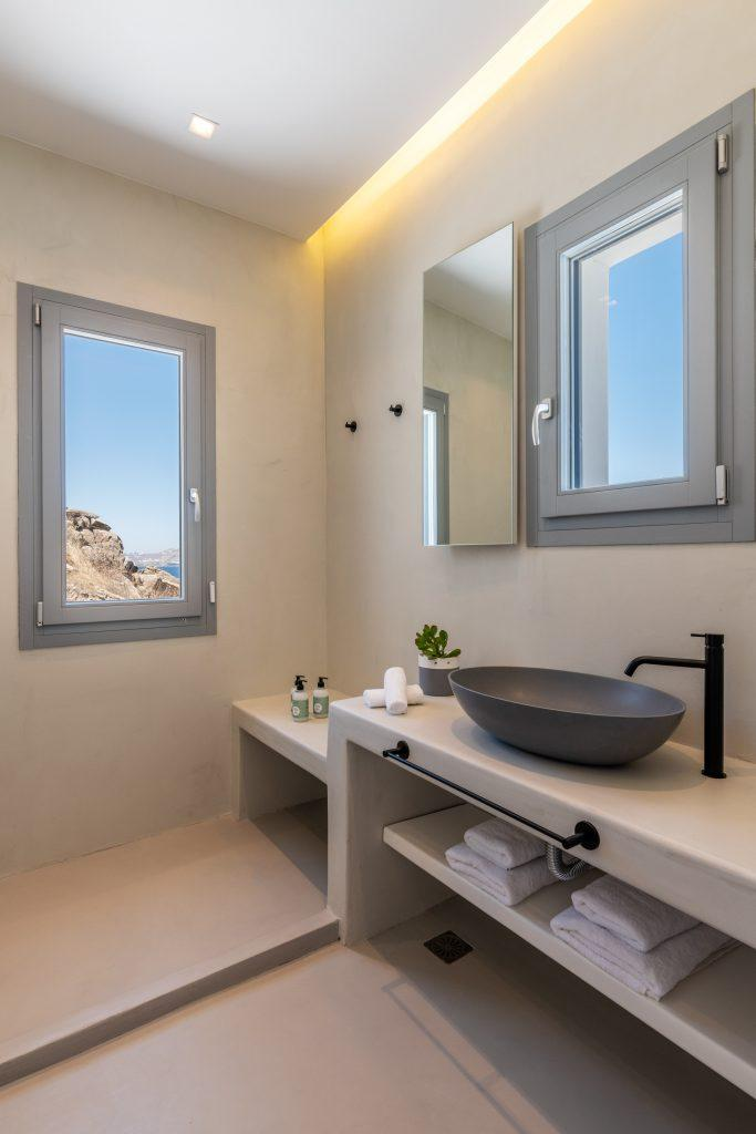 modern designed bathroom with white walls and gray sink