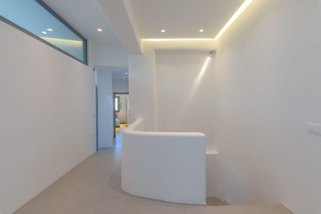 hallway of white walls lit by lamps and degree
