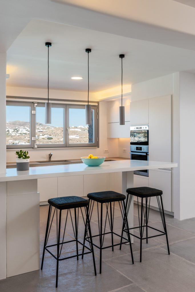 kitchen with white high-gloss elements and sleigh with black chairs