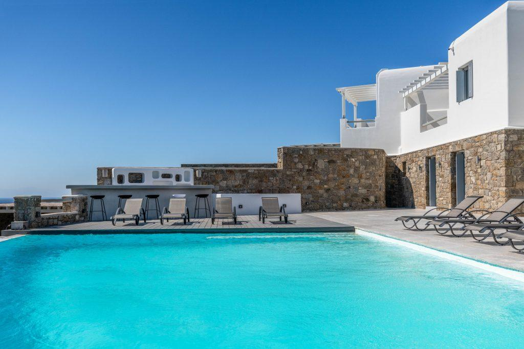 view of the villa with a mixture of white and stone walls with bar and cooling pool
