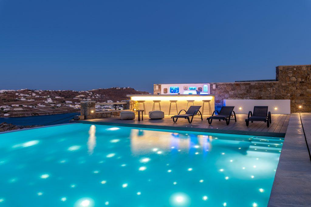 view of the starry sky and the illuminated city of Mykonos from the pool
