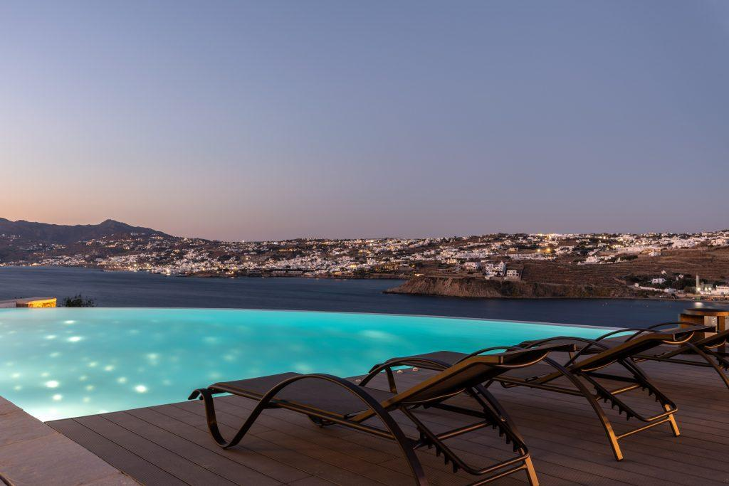 view of the sunset over the city of Mykonos from the pool