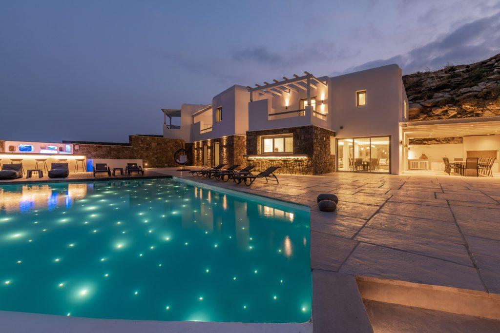night view of a luxury villa with a pool lit by tiny lamps that give the appearance of stars