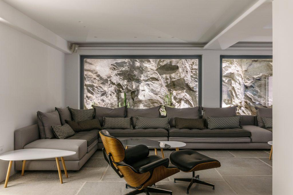 lighted stone walls and a large cozy set of gray furniture