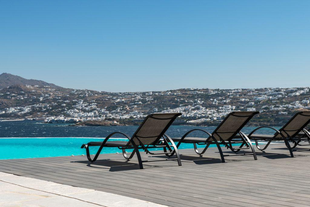 sea view with reflection of sunlight from the pool and comfortable deck chairs