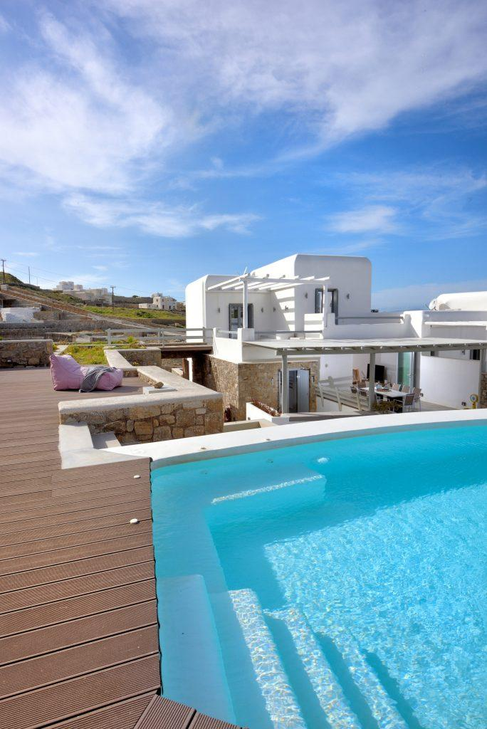 view of a white villa in daylight and a large cooling pool