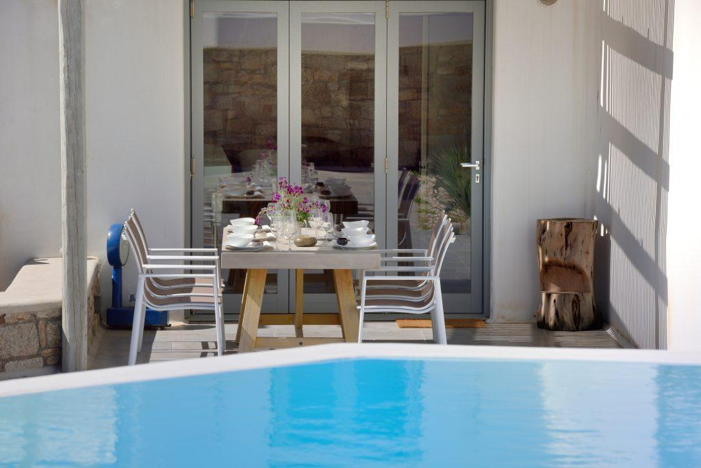 wooden table with comfortable chairs ideal for lunch by the pool