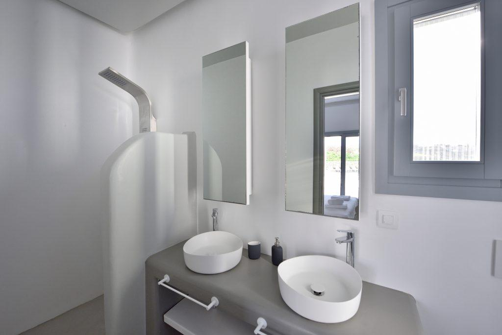 two large mirrors with a white sink and a toscabin