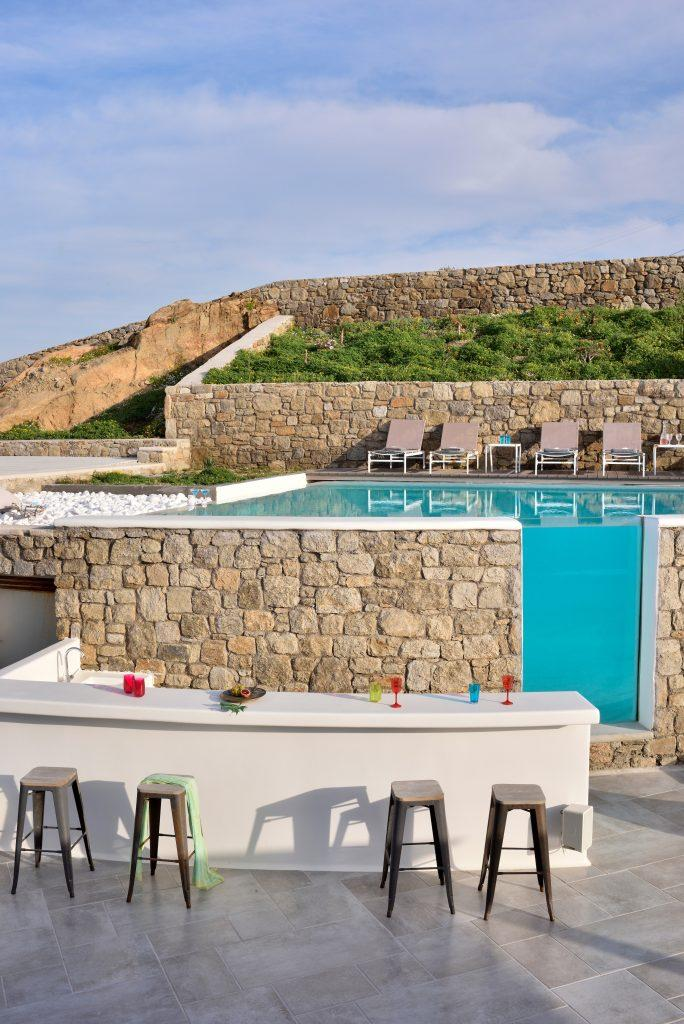 stone fence around the pool and a white bar with wooden chairs
