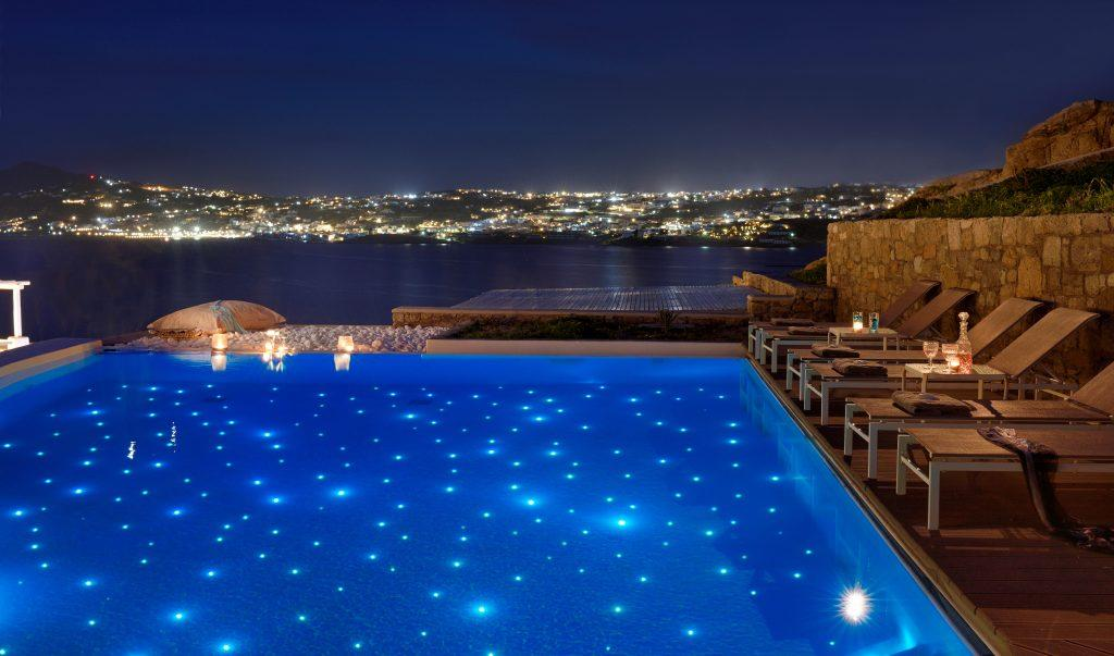 pool overlooking the sea with a reflection of the starry sky and the illuminated city of Mykonos