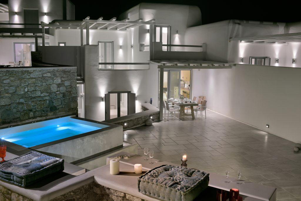 night view of a luxurious lighted villa with a spacious courtyard
