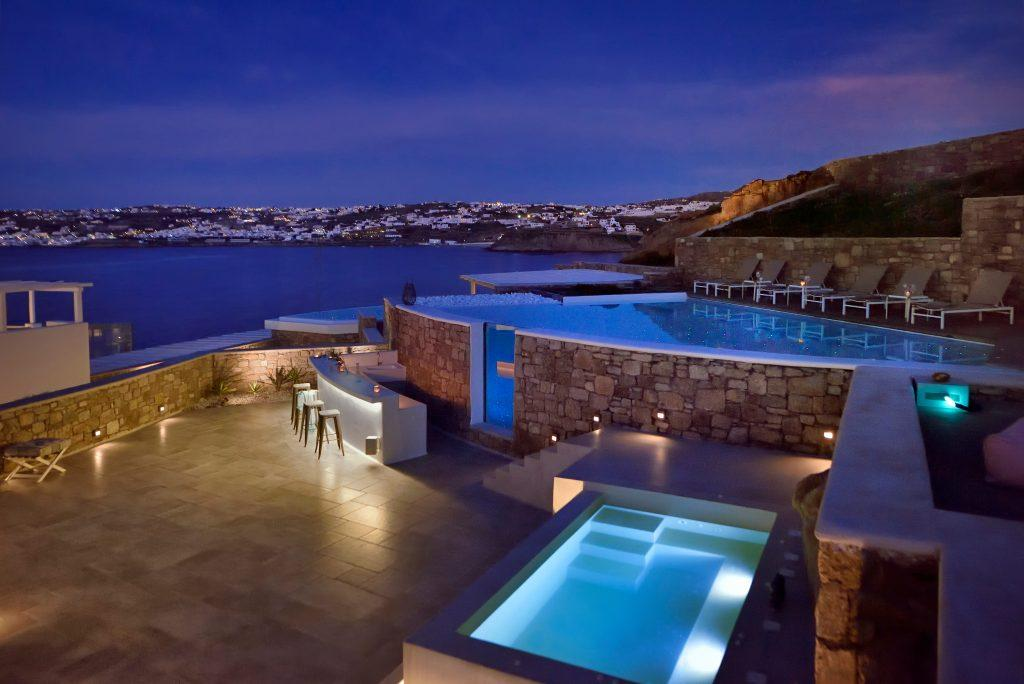 night view of the courtyard of the villa with two beautifully lit pools and a bar