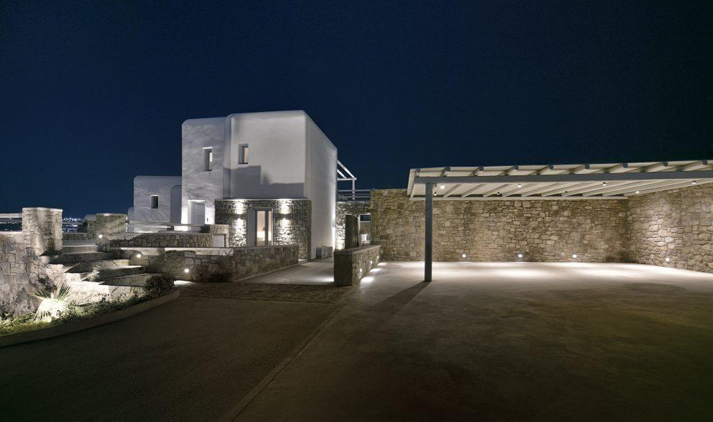 night view of a lighted villa with private parking