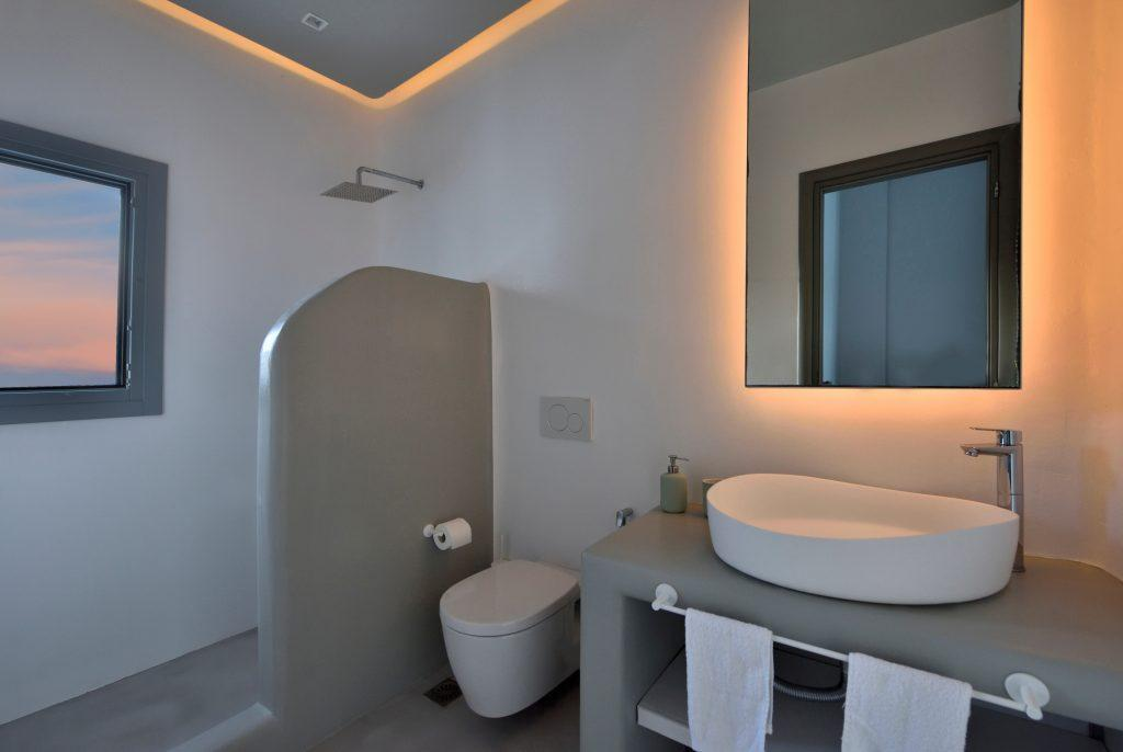 bathroom with shower and a small window with a gray wooden frame