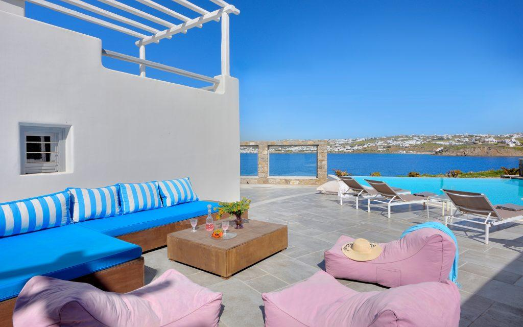 courtyard of the villa with blue garden furniture and comfortable pink pillows