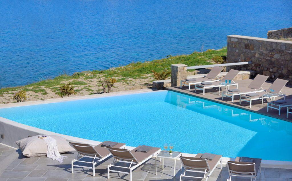 pool located near the sea with comfortable deck chairs