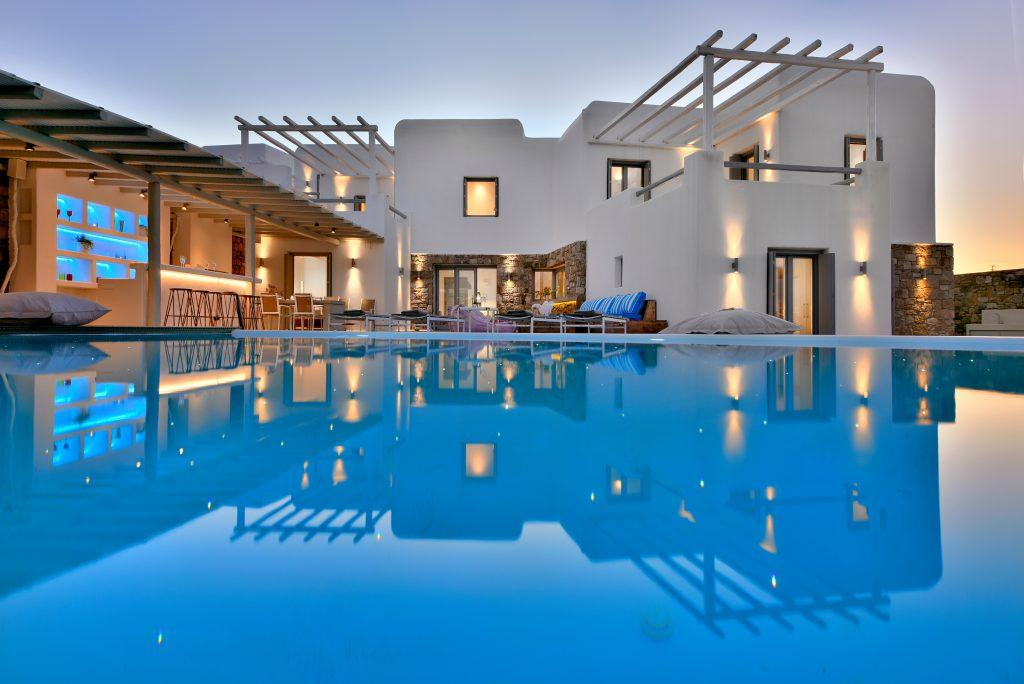 view of a villa that is dimly lit with an infinity pool