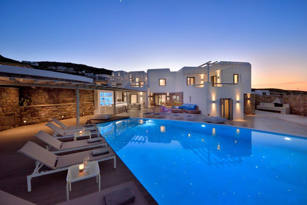 night view of a luxury white villa with pool and sunbeds lit by candles