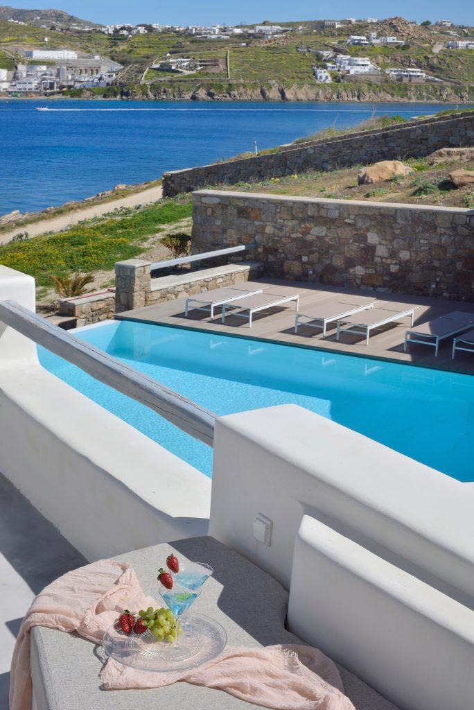 view from the balcony to the sea and the pool of the luxury villa while enjoying a refreshing drink