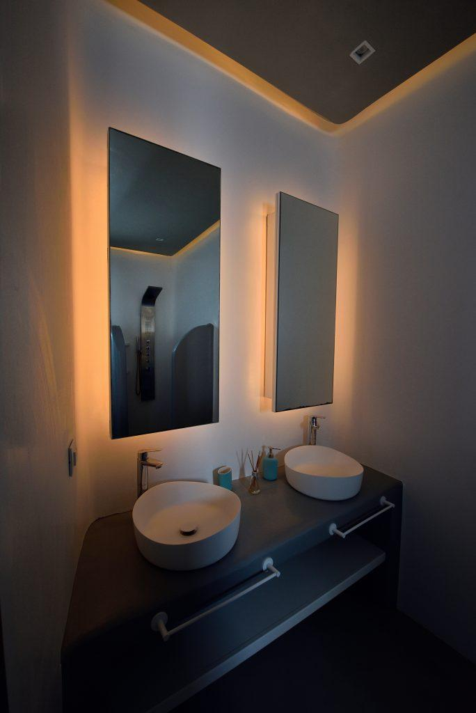 dim light in the bathroom with two sinks and mirrors
