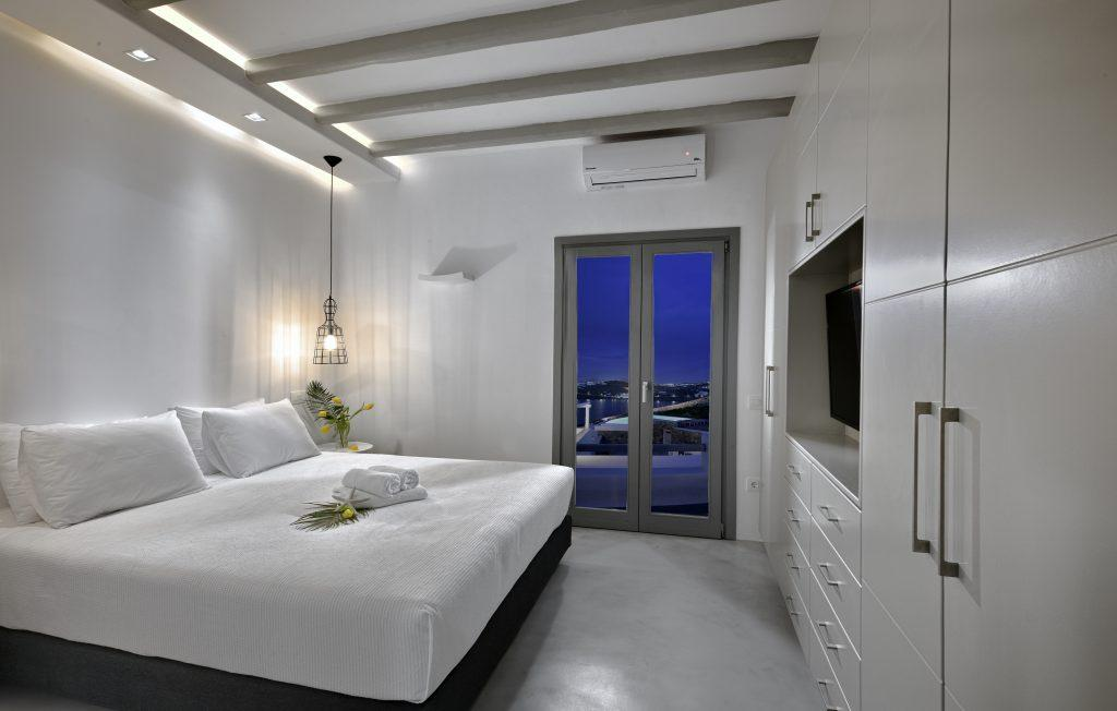 bedroom with a white comfortable bed and a decorative bouquet of yellow flowers