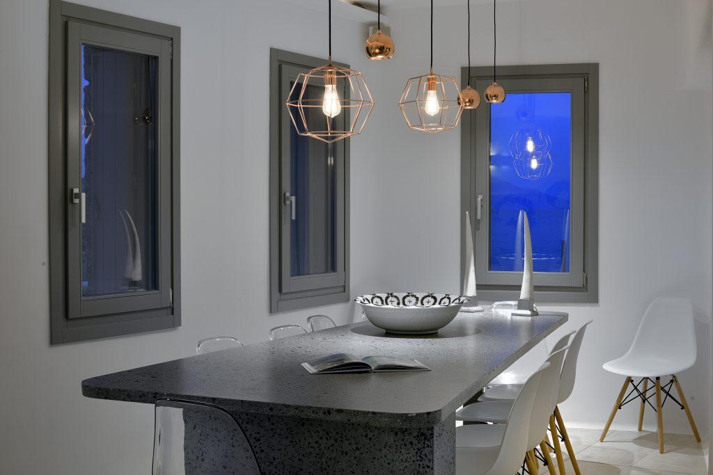 ceramic dining table in gray with white chairs and modern lamps