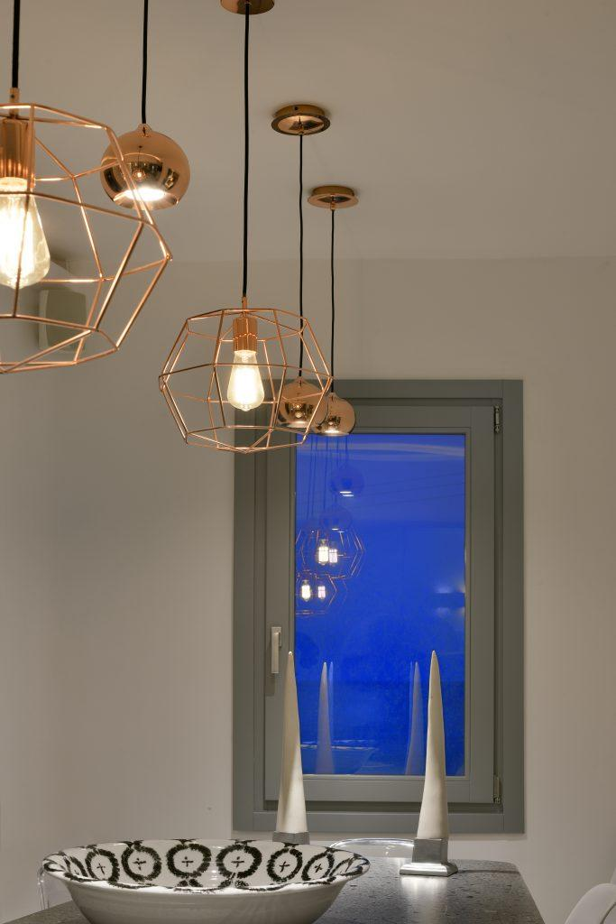 room with white walls and modernly designed chandeliers