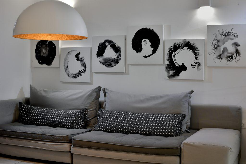 room with white walls and modern paintings that contribute to the atmosphere