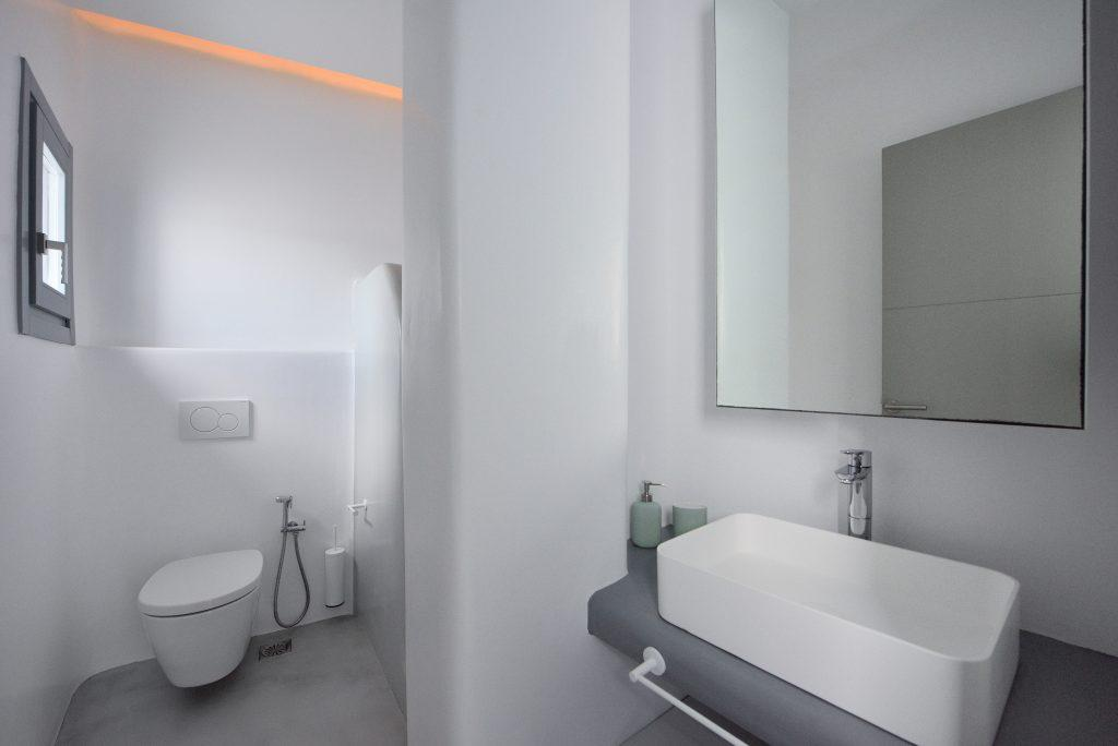 white walls and a ceramic sink with a mirror