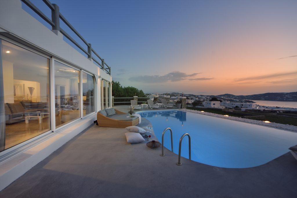 view of the sunset and a luxury villa with large windows that make that view accessible