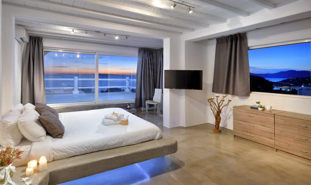 bedroom dimly lit with large windows overlooking the glistening blue sea