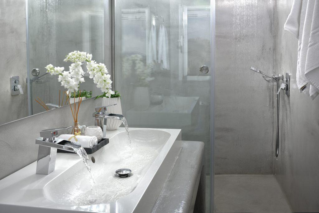 gray bathroom with large mirrors and a washbasin for two adorned with a bouquet of white flowers