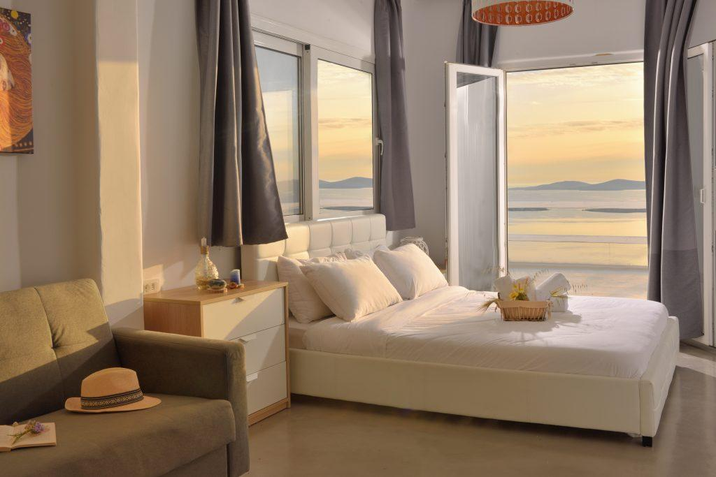 beautiful view of the sunset from a luxurious room with a white comfortable bed