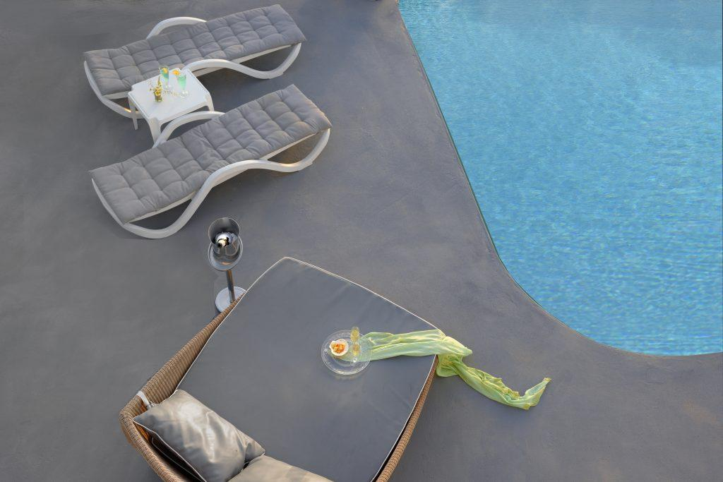 comfortable wicker loungers with gray pillows ideal for relaxing with a drink