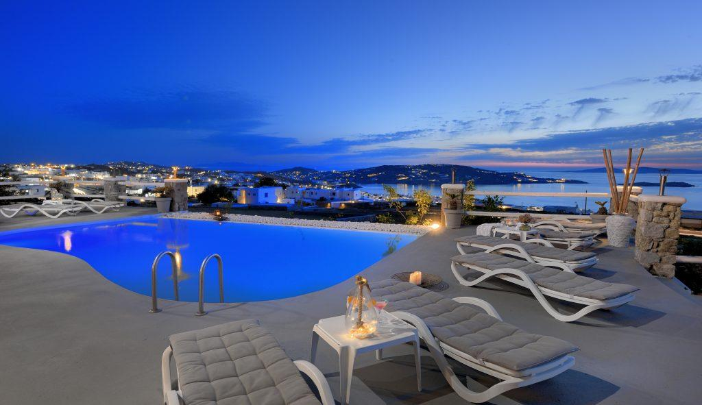 view of the blue sky above the sea and the illuminated city from the pool